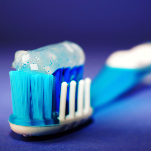 closeup of a a toothbrush and bristles with toothpaste